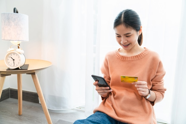 Beautiful asian woman holding credit card and smartphone with shopping online