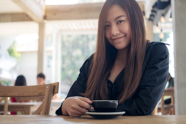 A beautiful asian woman holding and drinking coffee with feeling relaxed in cafe
