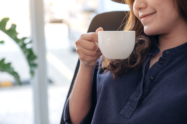 A beautiful asian woman holding and drinking hot coffee with feeling good in cafe