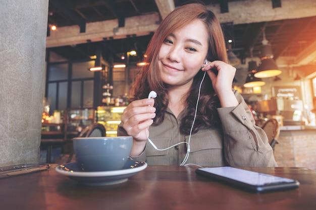 カフェで携帯電話で音楽を聴きながらイヤホンを保持している美しいアジアの女性