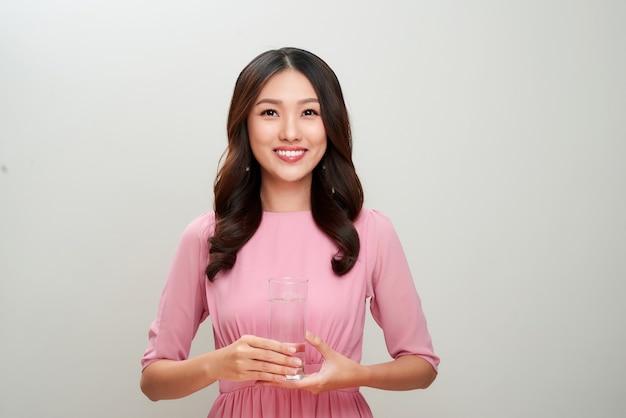 水のガラスを保持している美しいアジアの女性。ヘルスケアの概念。