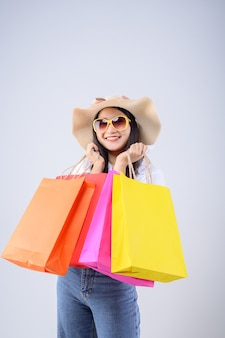 Beautiful asian woman holding a multi-colored shopping bag with a happy expression on white background.