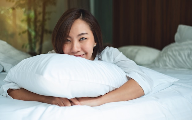 A beautiful asian woman holding a pillow while lying down on a white cozy bed at home