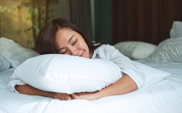 A beautiful asian woman holding a pillow while sleeping in a white cozy bed at home