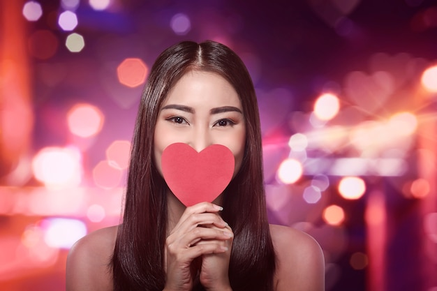Beautiful asian woman holding a red heart