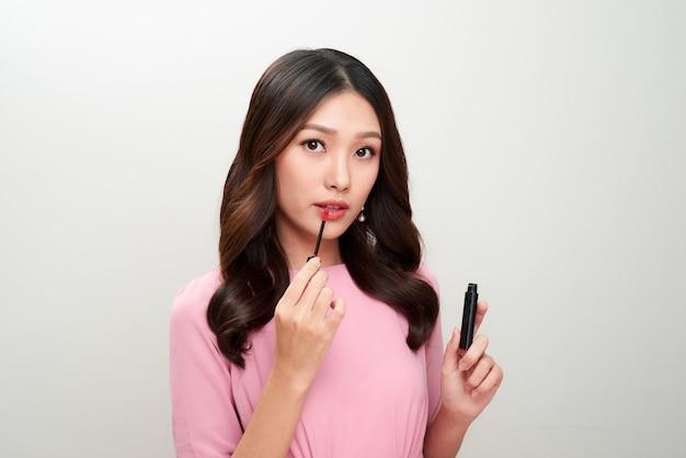 赤いリップグロスを保持し、それを適用する美しいアジアの女性