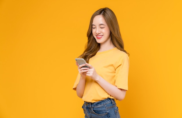 Beautiful asian woman holding smartphone and smiling with typing on mobile, light yellow background.