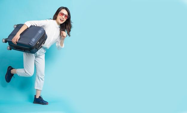 Красивая азиатская женщина, держащая чемодан на синем