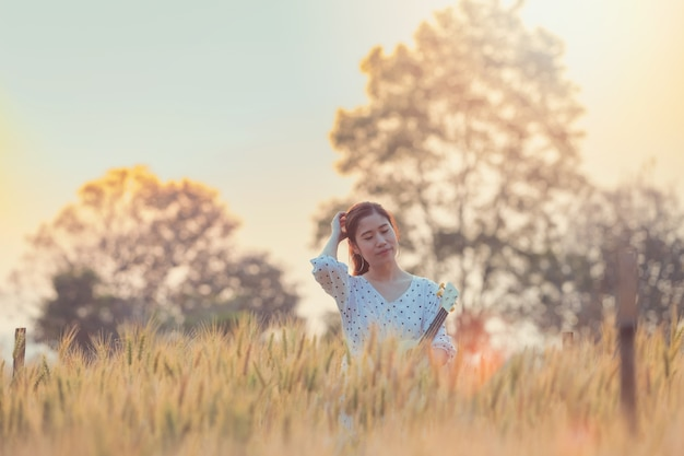 Beautiful asian woman holding ukulele and relaxing at barley field in summer on sunset time