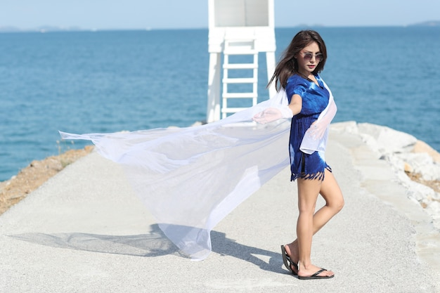Beautiful asian woman holding white cloth and enjoy holiday vacation on the beach