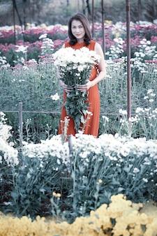 黄色い花を誇りを持って手に持つ美しいアジアの女性、フラワーガーデンの所有者は販売のための良質の花に満足しています。