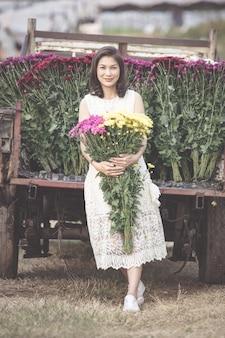 Красивая азиатская женщина с гордостью держит желтые цветы в руках, владелец цветочного сада доволен продажей цветов хорошего качества.