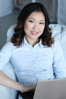 Bella donna asiatica a casa con il computer portatile