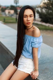 Красивая азиатская женщина в голубой летней блузке с белыми шортами в городе в летний день.