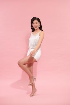 Красивая азиатская женщина в серебряном вечернем платье с блестками стоит