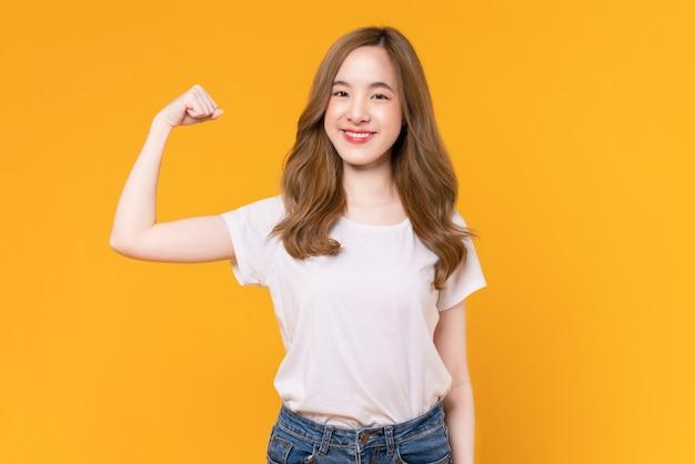 흰색 티셔츠를 입은 아름다운 아시아 여성은 팔과 주먹을 꽉 쥐고 강한 힘을 보여주며 승리를 축하하는 승리를 축하합니다.
