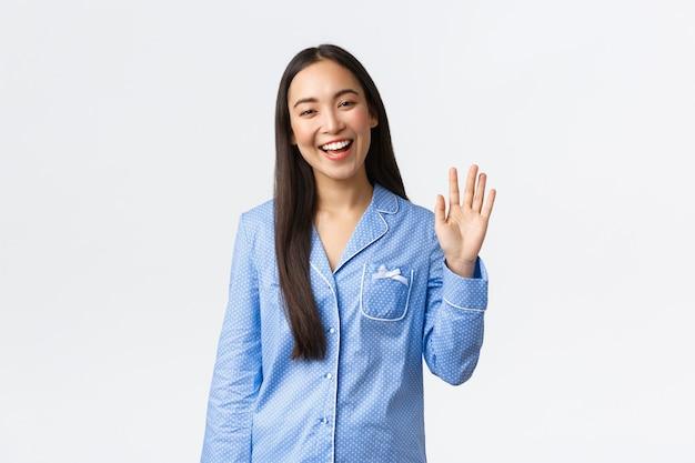 幸せに笑って、挨拶するために手を振って、ガールフレンドに挨拶し、寝坊パーティーへようこそ、こんにちはジェスチャーで白い背景、白い背景を立っている青いパジャマの美しいアジアの女性。