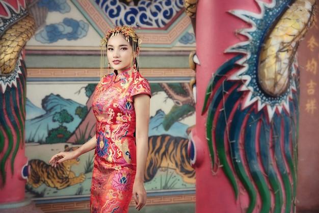 중국 새 해에 축하 제스처와 함께 전통적인 중국 드레스에서 아름 다운 아시아 여자