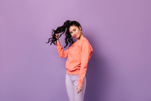Красивая азиатская женщина в серьгах стоя на фиолетовой предпосылке. студия выстрел очаровательной кудрявой китайской женщины, играющей с волосами.