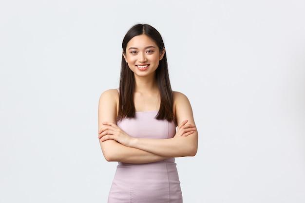 Красивая азиатская женщина в элегантном платье присутствует на официальной вечеринке компании, праздничном мероприятии