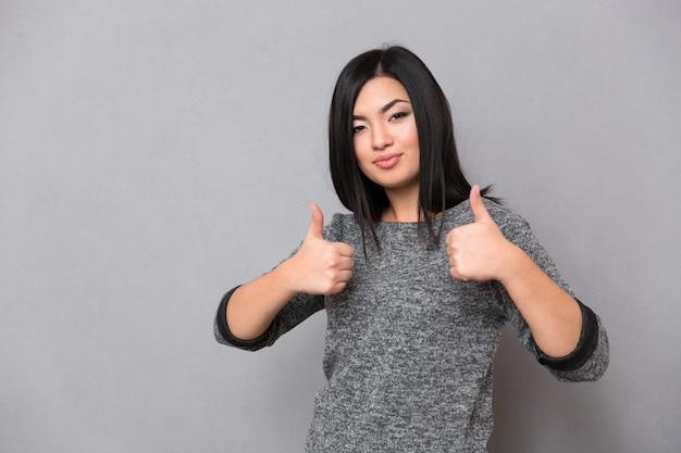 親指を立てて正面を見て灰色のジャンパーで美しいアジアの女性
