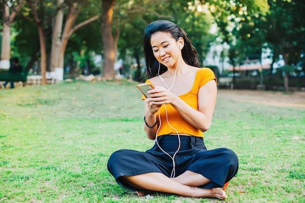 홍콩의 아름다운 아시아 여성이 휴대전화 앱을 사용하여 음악을 듣고 있다