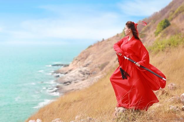 Красивая азиатская женщина в красном китайском костюме с черным мечом