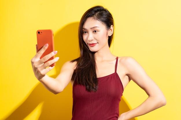 赤い水着と黄色の壁に電話を使用して美しいアジアの女性