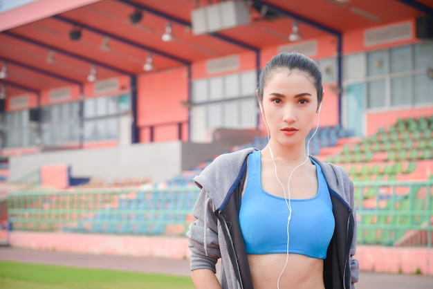 도시에서 야외 운동 후 이어폰에서 음악을 듣고 운동복에 아름 다운 아시아 여자.