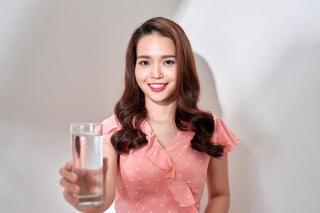 白い背景に飲み物用のガラスに水を入れた甘いピンクのドレスを着た美しいアジアの女性、新鮮な体のために飲む