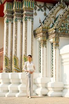 매우 엘리트하고 오래된 패션 인 태국 전통 의상을 입은 아름다운 아시아 여성. 여행 관광에 대 한 복고풍 건축과 공공 지역 와트 사원에 레이디.