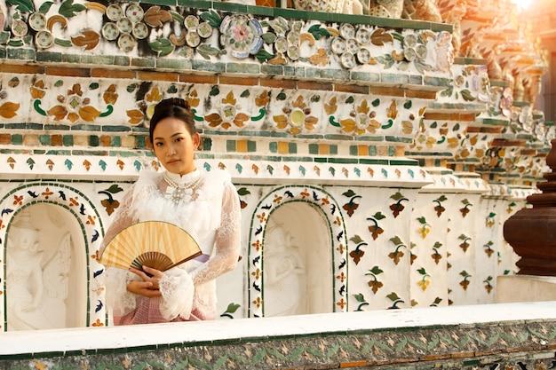 非常にエリートで古いファッションであるタイの伝統的な衣装の美しいアジアの女性。旅行観光のためのレトロな建築の公共エリアワット寺院の女性。