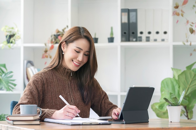 Красивая азиатская женщина в свитере шерстей работая на планшете и документе пока сидящ в офисе.