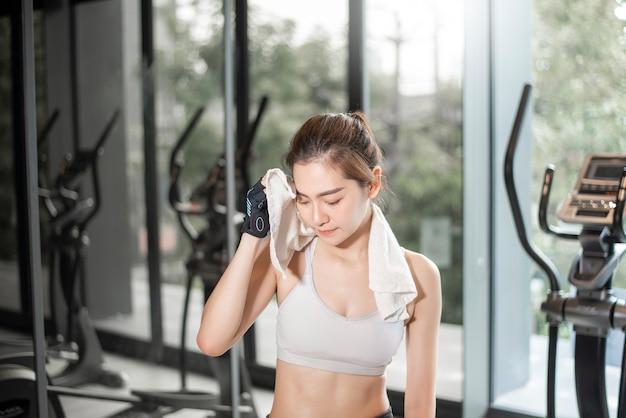 아름 다운 아시아 여자는 체육관에서 운동을하고있다