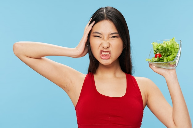 Beautiful asian woman is fed up with eating salad every day