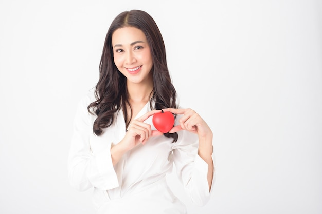 Beautiful asian woman is holding red heart (health care concept)