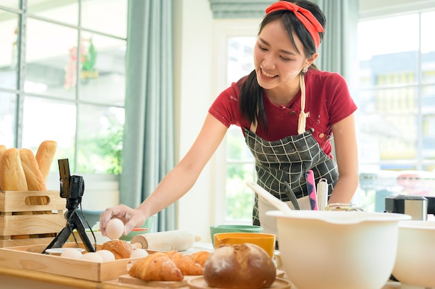 A beautiful asian woman is making bakery ,   live streaming or recording video on social media in her house