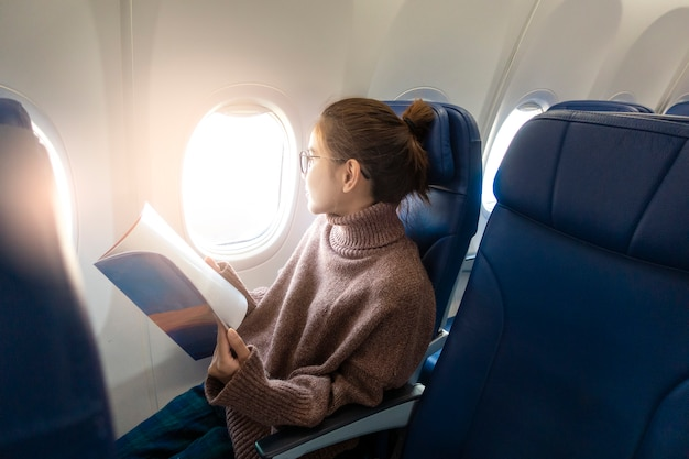 Beautiful asian woman is reading magazine in airplane