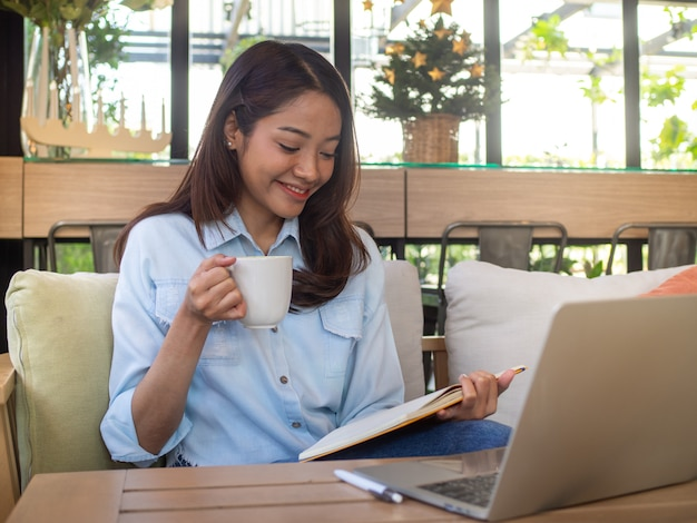 A beautiful asian woman is sitting reading a book on the sofa. holding a coffee and smiling relaxed