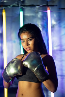 Beautiful asian woman is training and punching with silver gold mitts gloves. office girl exercises in modern color neon muay thai boxing gym with sweat water splash