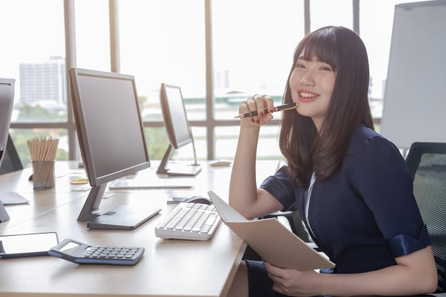 A beautiful asian woman is wearing a dark blue suit sitting at a desk in a modern office and is happy to work and has a large glass window background.