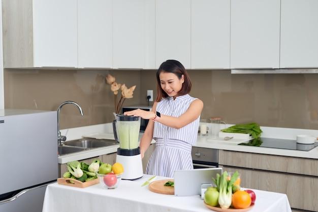 家庭の台所でジュースマシンで青汁を作るジューサーの美しいアジアの女性。健康的なコンセプト。