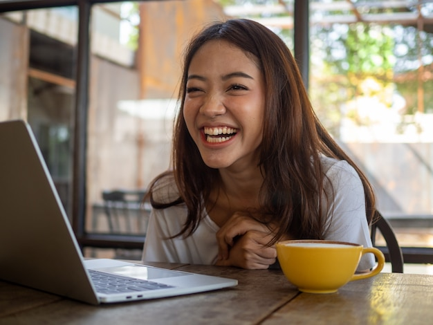 Beautiful asian woman laughed happily while sitting in a cafe