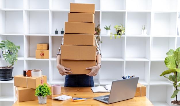 많은 소포를 들어 올리는 아름다운 아시아 여성, 그녀는 온라인 상점을 소유하고 개인 운송 회사를 통해 포장하고 배송합니다. 온라인 판매 및 온라인 쇼핑 개념입니다.