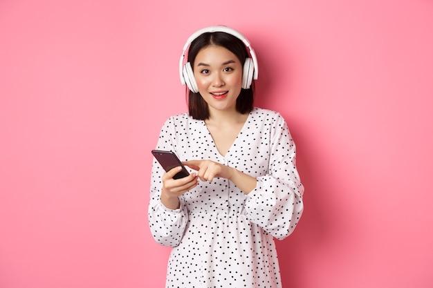 Красивая азиатская женщина слушает музыку в наушниках, используя мобильный телефон, улыбаясь счастливой в камеру, стоя на розовом фоне