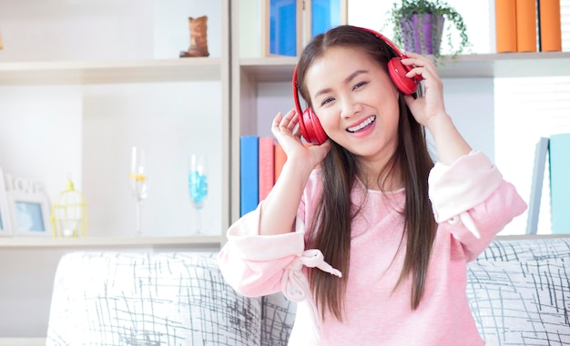 Beautiful asian woman listening to music with headphones