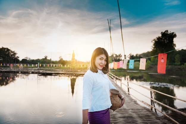 Beautiful asian woman in local dress holding fishing trap standing on bamboo bridge in ric
