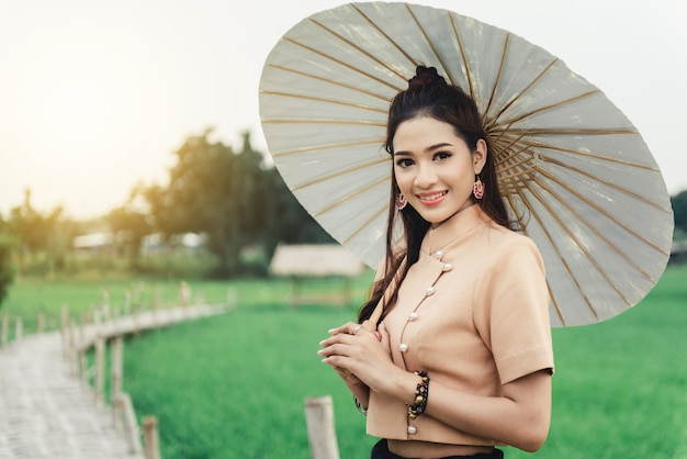 Beautiful asian woman in local dress holding paper umbrella standing