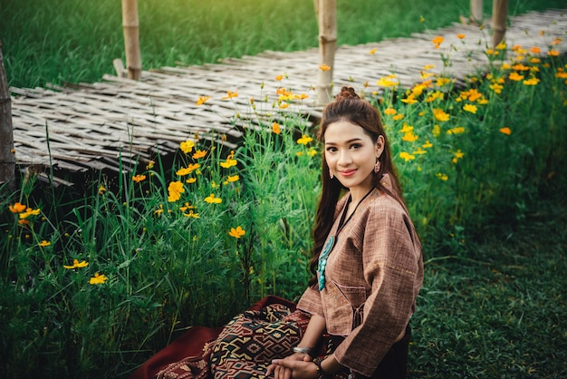 Beautiful asian woman in local dress sitting on ground and enjoy natural  in rice field