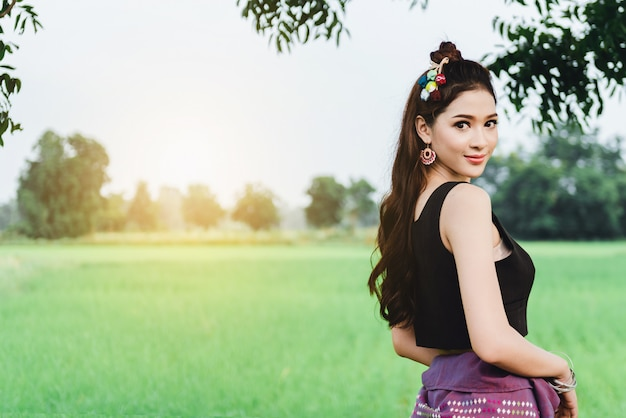 Beautiful asian woman in local dress standing and enjoy natural on bamboo bridge in rice field